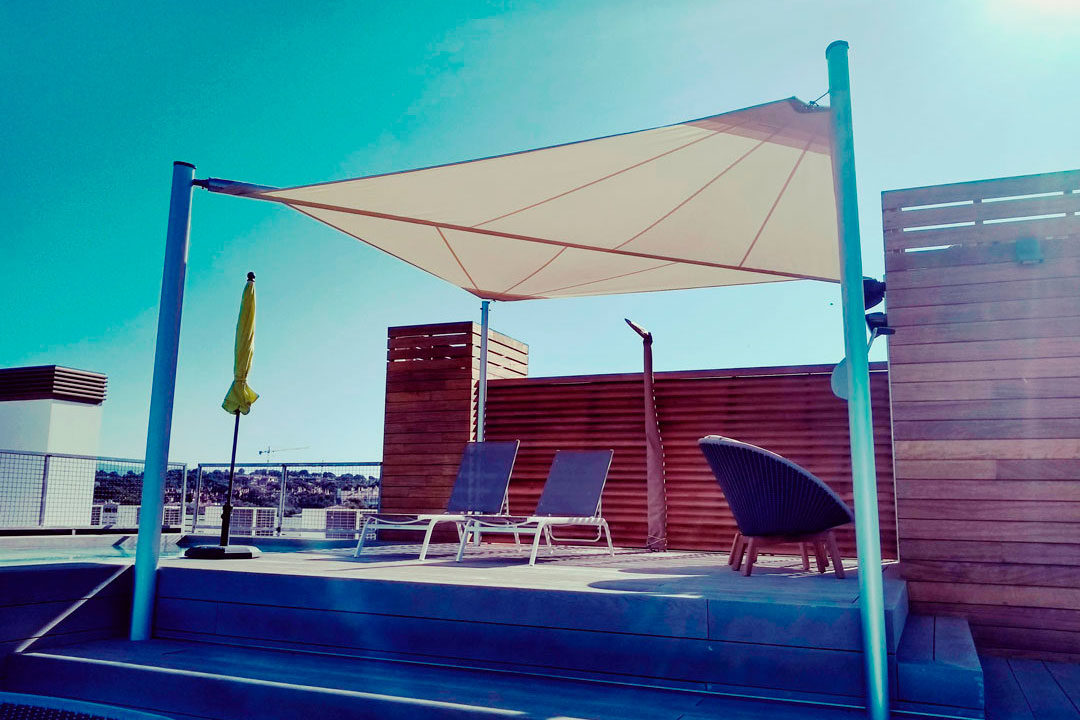 Motorised roll-up sun sail on a rooftop in Cap Adriano